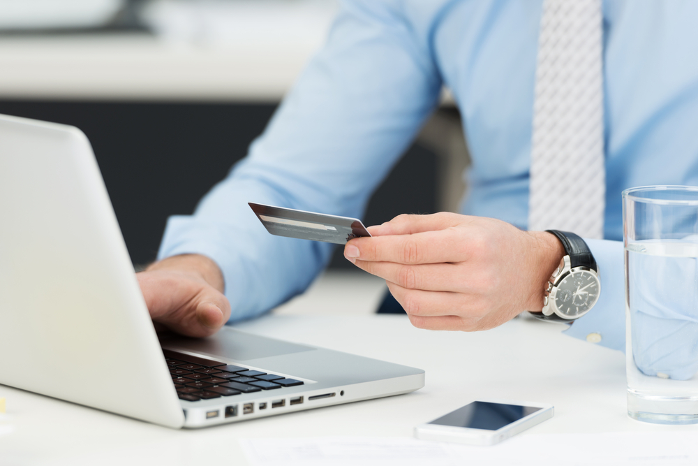 Businessman in need of debt support entering his credit card details on a laptop