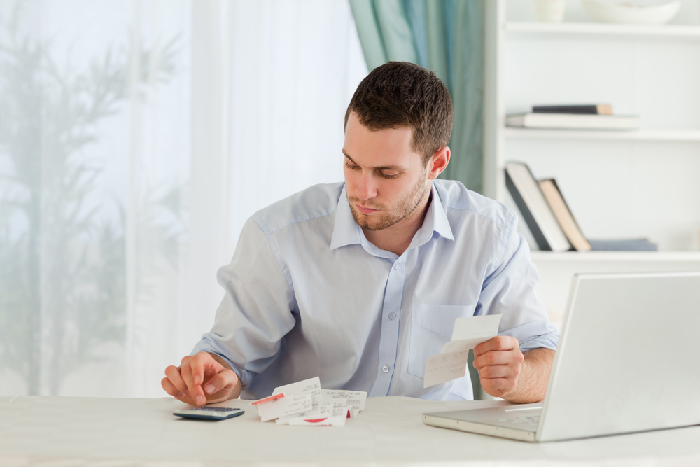 Young businessman in need of debt support calculating bills from receipts