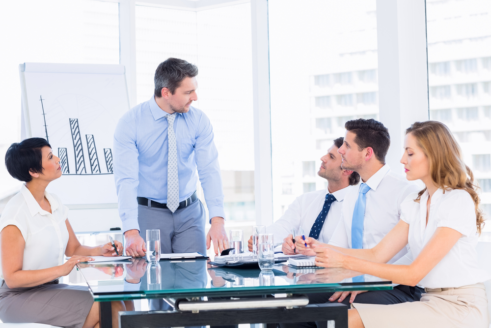 A business director in a meeting with colleagues to represent boardroom disputes