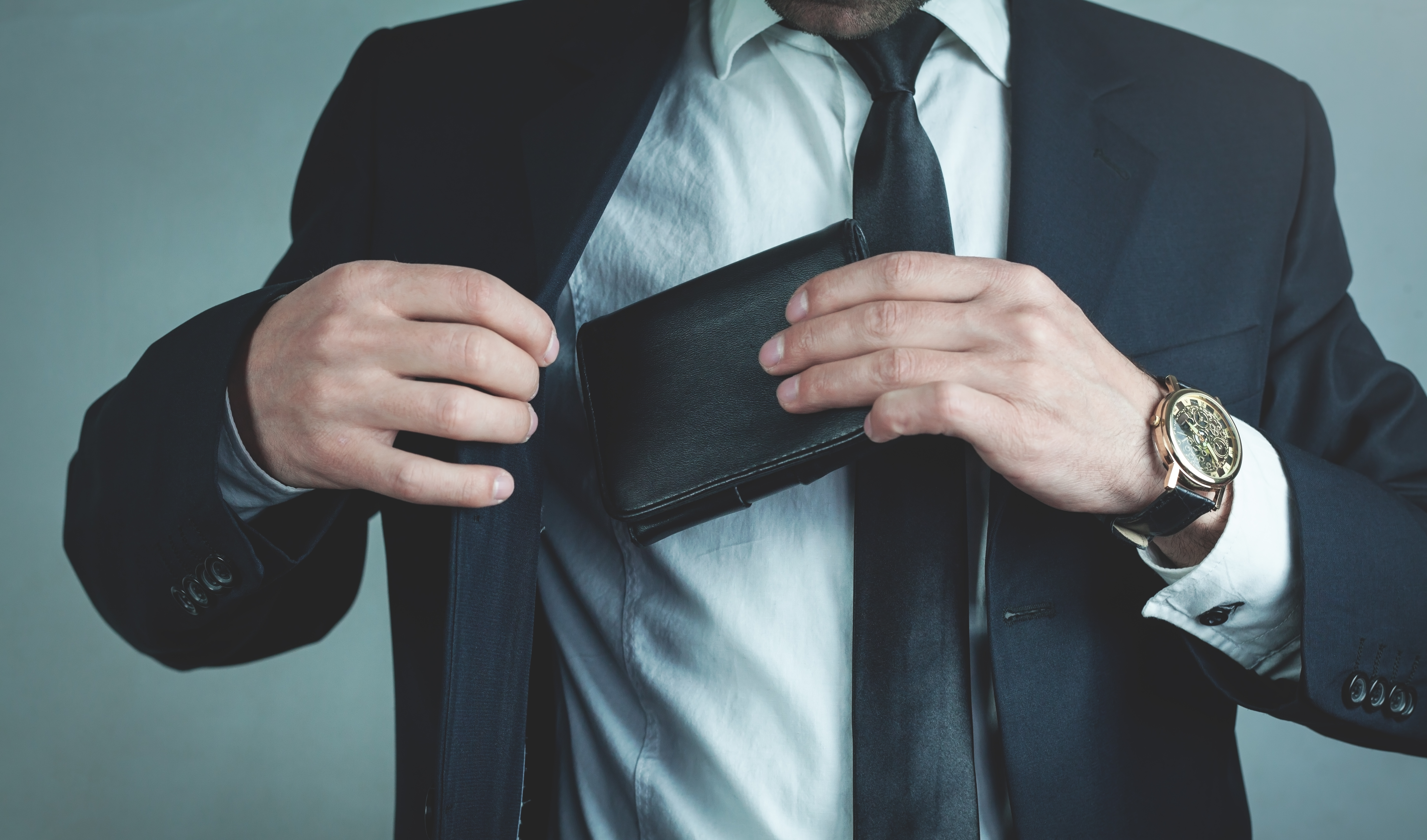 Businessman pulls his leather wallet into suit pocket, representing S455 tax on liquidation